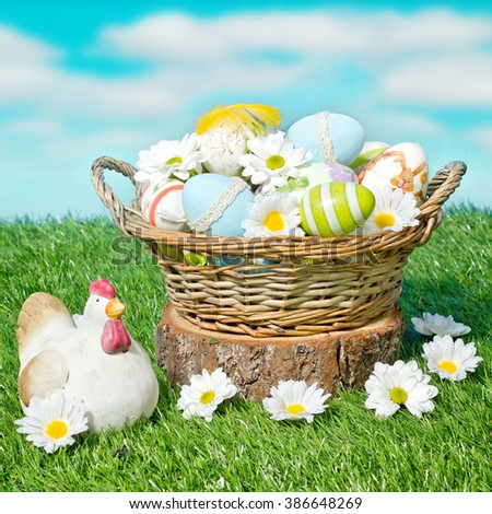 decorated easter eggs in the basket with daisies - stock photo