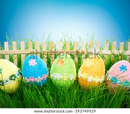 Decorated easter eggs in the grass on blue background