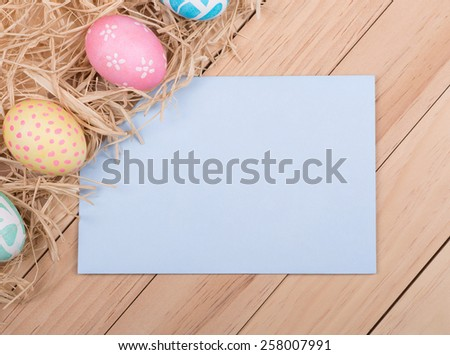 Decorated Easter eggs next to envelope on a wood background - stock photo
