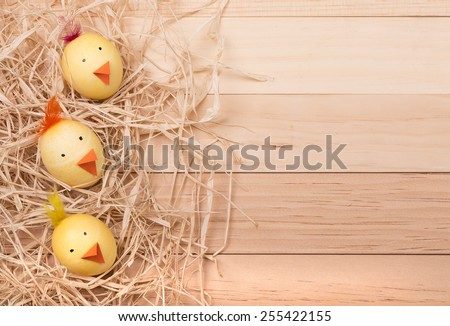 Decorated Easter eggs to look like chicks on a wood background for copy space - stock photo