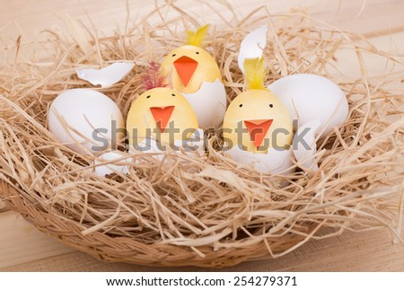 Decorated easter eggs to look like hatching chicks in a basket stock