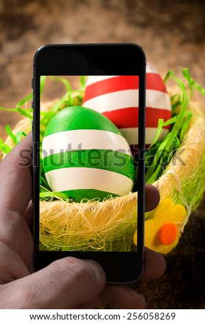Decorated Eastern eggs in the basket shoot by mobile phone camera.Selective focus on the front egg - stock photo