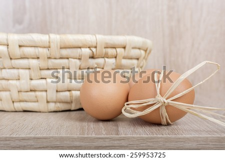 Decorated fresh eggs next to the woven basket on a wooden background - stock photo
