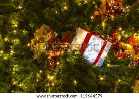 Decorated gift box on the Christmas tree - stock photo