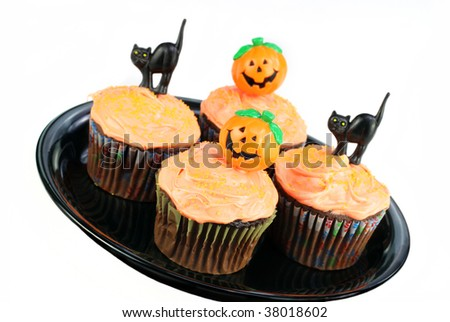 Decorated Halloween cupcakes on a black plate on a white background.  Copy space available. - stock photo