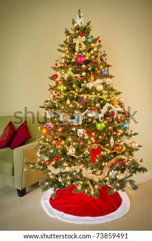 Decorated holiday tree beside sofa - stock photo