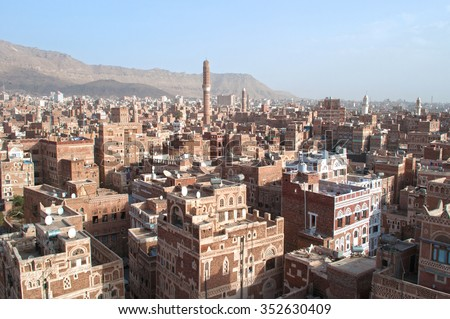 Decorated houses, palaces, minarets and the Saleh Mosque in the fog, the Old City of Sana'a, Republic of Yemen, Unesco world heritage site with unique architectural characteristics - stock photo