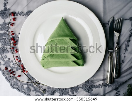 Decorated Plate on rustic wooden Table with silvereware and Napkin - stock photo