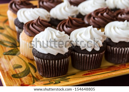 Decorated platter of chocolate and vanilla frosted cupcakes close up - stock photo