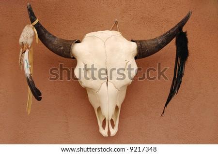 Decorated Pueblo bull skull on adobe wall - stock photo