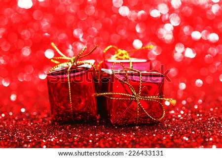 Decorated red holiday gifts on glitter background - stock photo