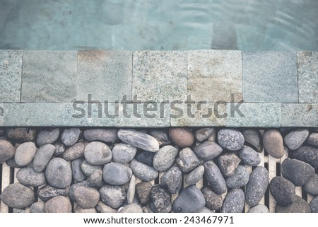 Decorated stones beside the pool - stock photo