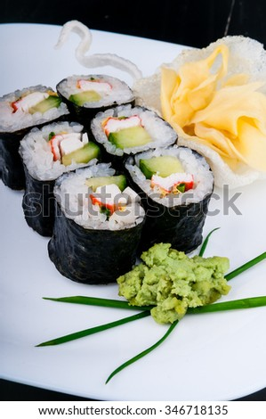 Decorated sushi served on a white plate. The meal is ready for eating.