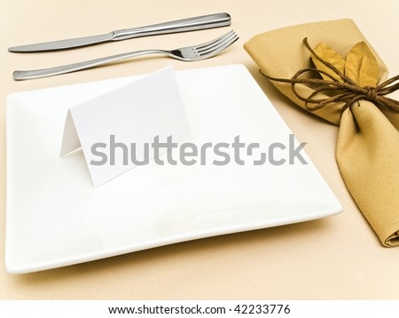 decorated table serving with golden bay leaves in serviette and cord near plate, knife and fork at beige - stock photo