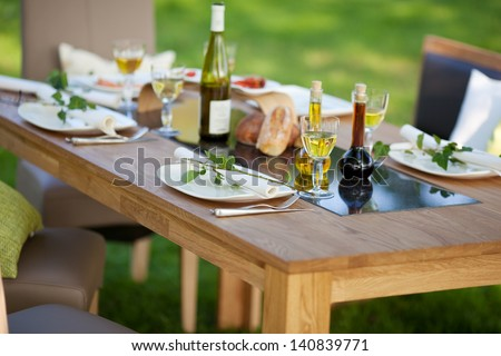 decorated table with dinner in the garden - stock photo