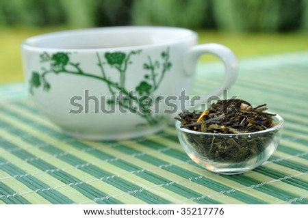 Decorated teacup and a glass container full of fresh leaves on a garden table - stock photo