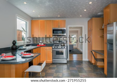 Decorated Traditional designed kitchen with wooden cabinets, stainless steel appliances and granite. - stock photo