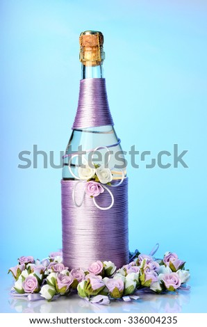 Decorated wedding bottle of champagne with roses, isolated on white background  - stock photo