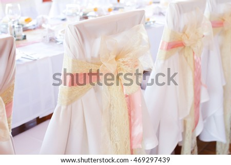 decorated wedding chair with pink ribbon