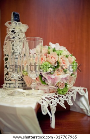 Decorated wedding champagne bottles, decorated glasses and wedding bridal bouquet on the table with a lace tablecloth