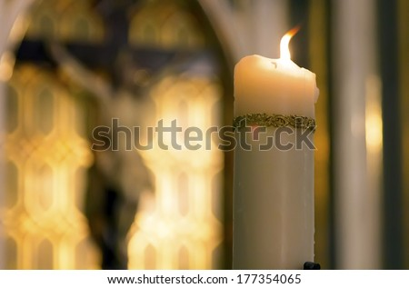 decorated white candle burning inside a Catholic with the image of Christ behind Church - stock photo