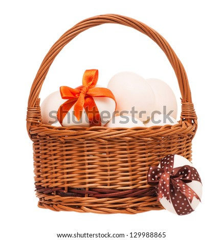 Decorated white eggs in a wicker basket isolated on white background