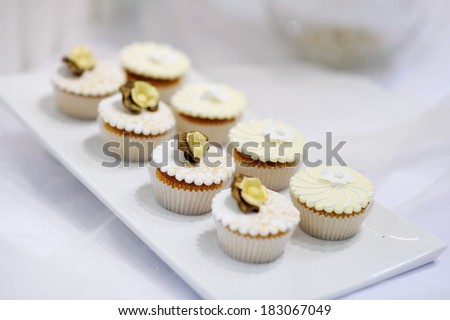 Decorated white vanilla cream cupcakes on a white plate - stock photo