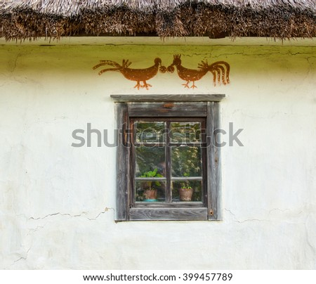 Decorated window of the old traditional Ukrainian house built in wattle and daub technique with thatched roof. - stock photo