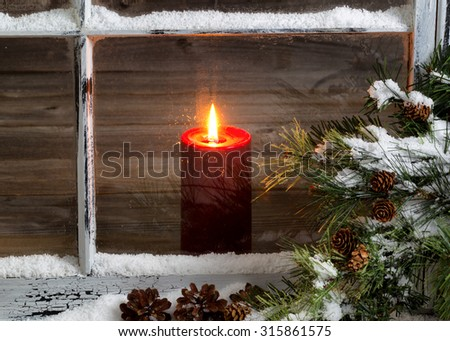 Decorated window with glowing red candle, selective focus on flame and top part of candle, pine tree, cones and snow outside. Christmas concept. - stock photo