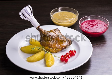 decorated with duck leg garnished with roasted potatoes with sauce - stock photo