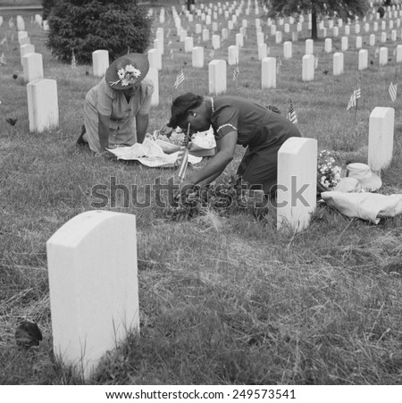 Decorating a soldier's grave on Memorial Day in one of the African American sections. Arlington National Cemetery, Virginia. May 1943. - stock photo