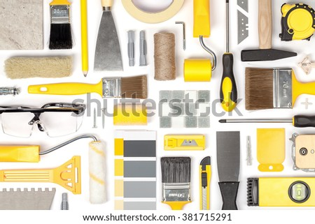 decorating and house renovation tools and other essentials on white background top view. flat lay composition in yellow colors - stock photo