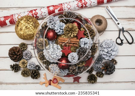 Decorating Christmas table with pine cones  - stock photo