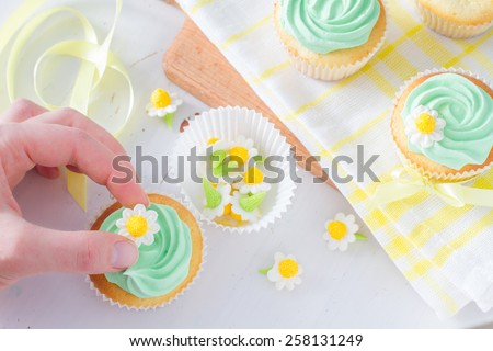 Decorating cupcakes with flower sugar figures, plaid napkin, wood board, white wood background - stock photo