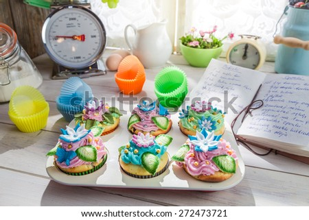 Decorating delicious cupcakes with cream and decoration - stock photo