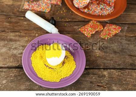Decorating Easter egg on color plate on wooden table, closeup - stock photo