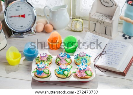 Decorating fresh cupcakes with cream and decoration