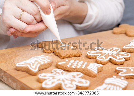 Decorating gingerbread cookies (bear) with white icing, selective focus and place for text - stock photo