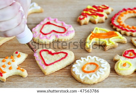 Decorating homemade shortbread cookies with icing from piping bag - stock photo