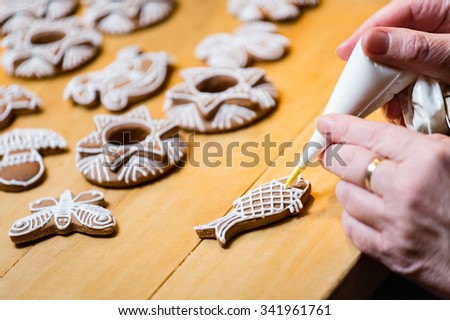 Decorating the traditional Christmas gingerbread cookies - stock photo