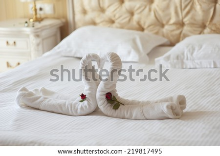 decoration beds in the hotel two swans and heart of polotets - stock photo
