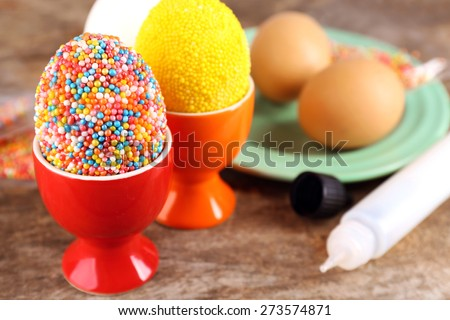 Decoration Easter eggs with colorful beads on wooden table, closeup - stock photo