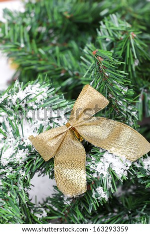 Decoration golden billow on new year tree branch in snow