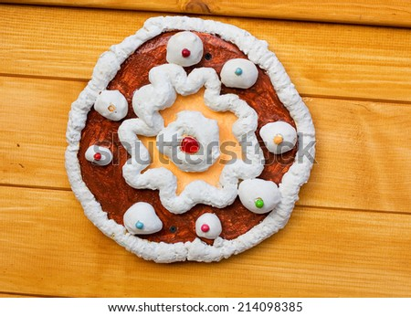 Decoration in the form of cake with cream and berries on the wooden wall - stock photo