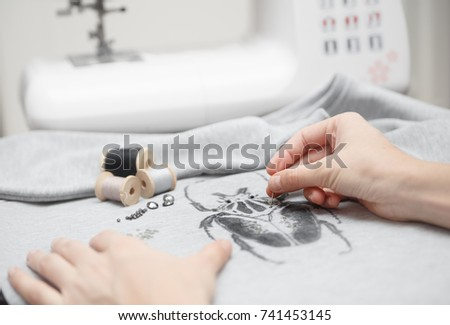 Decoration new sweatshirt. Sewing process. Women's hands behind her sewing. Sewing machine with sewing tools
