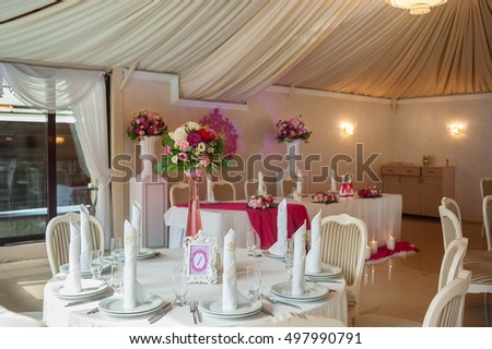 Decoration of a wedding with fresh flowers. Composition from fresh flowers in a high glass vase for tables of guests and number of a table in a beautiful white frame