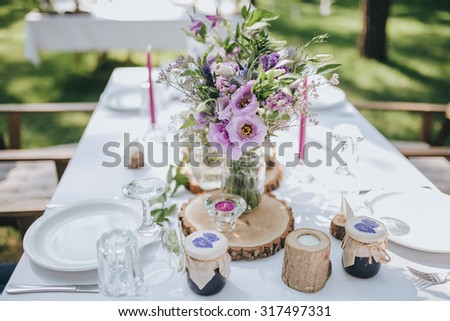 decoration of flowers, herbs and wooden elements on a festive table with a white cloth, which stands on a green lawn in the forest - stock photo