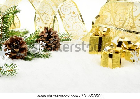 Decoration of gold christmas gifts, gold ribbon on snow christmas tree branch on white - stock photo