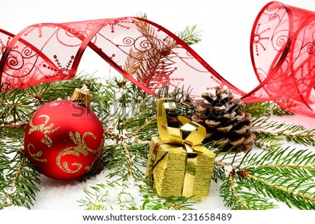 Decoration of gold christmas gifts,red ribbon and bauble on snow with pine cones, christmas tree branch on white - stock photo