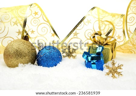 Decoration of golden and blue christmas baubles and gifts with ribbon on snow white background - stock photo